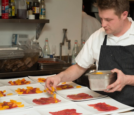 Chef Curtis di Fede plating tuna crudo in the Beard House kitchen